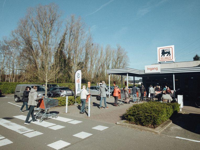 Aanschuiven aan de Delhaize, nu het aantal klanten in de winkel beperkt wordt. Beeld Thomas Sweertvaegher