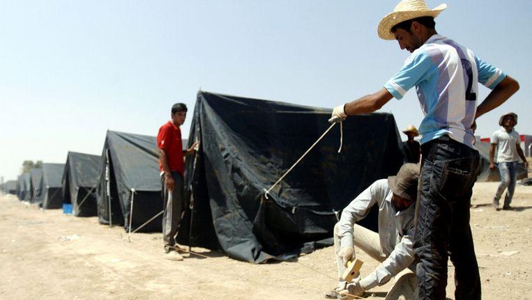 Medewerkers van UNCHR zetten een tentenkamp op voor Iraakse christenen die gevlucht zijn voor IS. Beeld epa