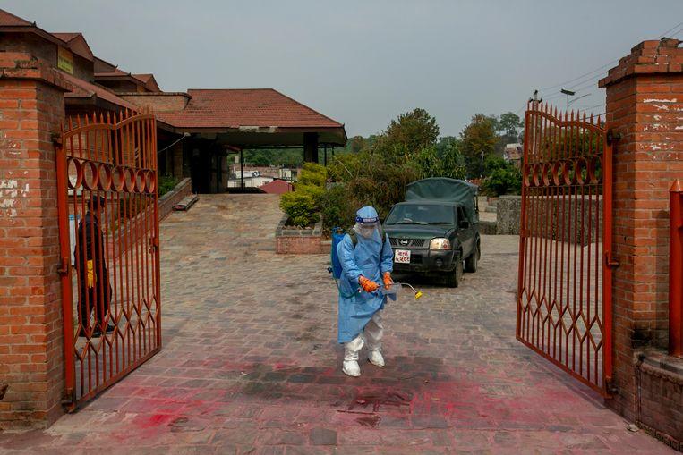 De ingang van een crematorium in Kathmandu wordt gedesinfecteerd. Op die plek werden de lichamen van slachtoffers neergelegd.  Beeld AP