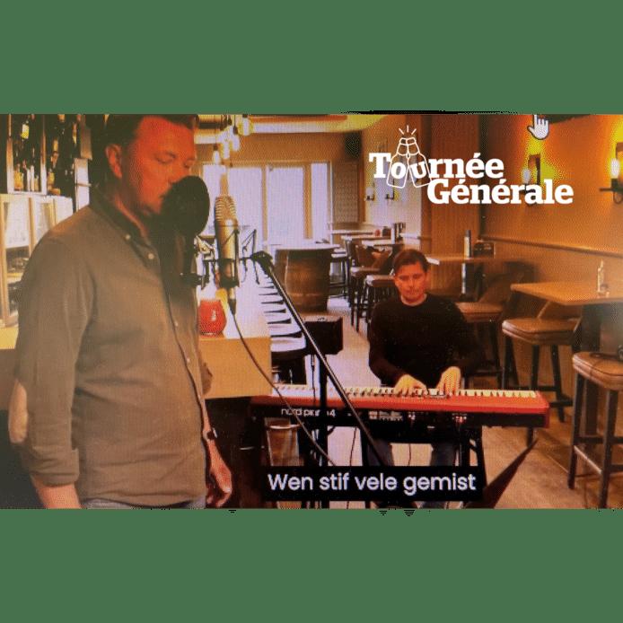 Uitbater Tom Sintobin van café Koornmarkt achter de micro, met assistentie van Karel Rommel achter de piano.