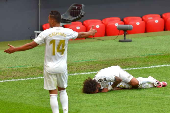 Real Madrid's Brazilian defender Marcelo (R) lies on the ground after falling during the Spanish League football match between Athletic Club Bilbao and Real Madrid at the San Mames stadium in Bilbao on July 5, 2020. (Photo by ANDER GILLENEA / AFP)
