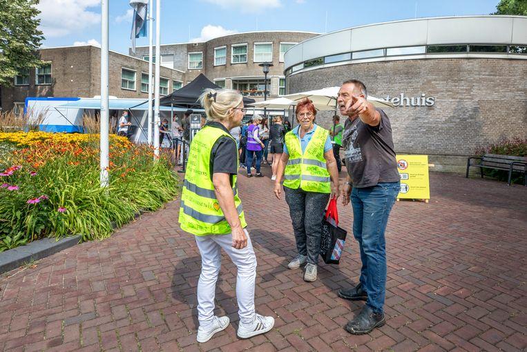 Confrontatie tussen een man die  pro-vacccinatie is (midden) en tegenstanders van vaccinatie in de gele hesjes bij prikbus in Lekkerkerk.  Beeld Raymond Rutting / de Volkskrant