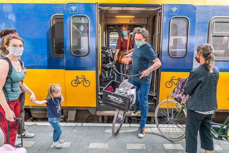 Theo van Meerendonk en Saskia Ruijter halen hun fietsen uit de trein. Beeld Joris van Gennip