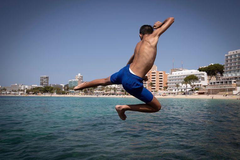 A youth jumps into the sea near Magaluf Beach in Calvia on the Spanish island of Mallorca on July 8, 2020. - The Balearic Islands are expecting a wave of tourists from the United Kingdom in the coming days as a 14-day quarantine requirement is due to be lifted ahead of the weekend. More than 18 million British tourists visited Spain last year, accounting for more than a fifth of the overall total of nearly 84 million visitors, figures from the National Institute of Statistics show. (Photo by JAIME REINA / AFP) Beeld AFP