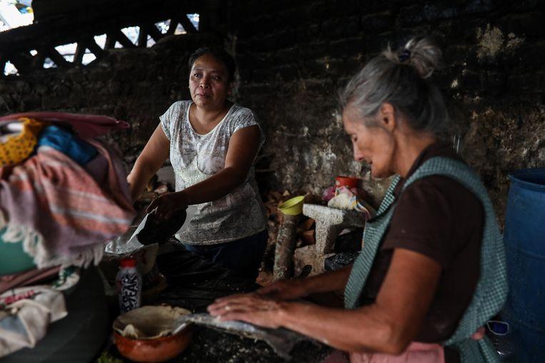 De moeder (links) en oma van de verdwenen Christian Rodríguez maken tortilla's. Beeld Felix Marquez