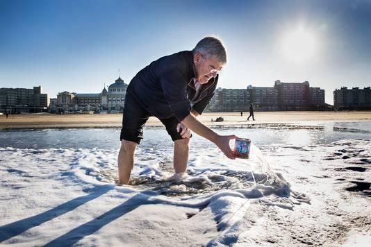 De Haagse burgemeester Jan van Zanen schept alvast een blik zeewater voor de alternatieve duik.