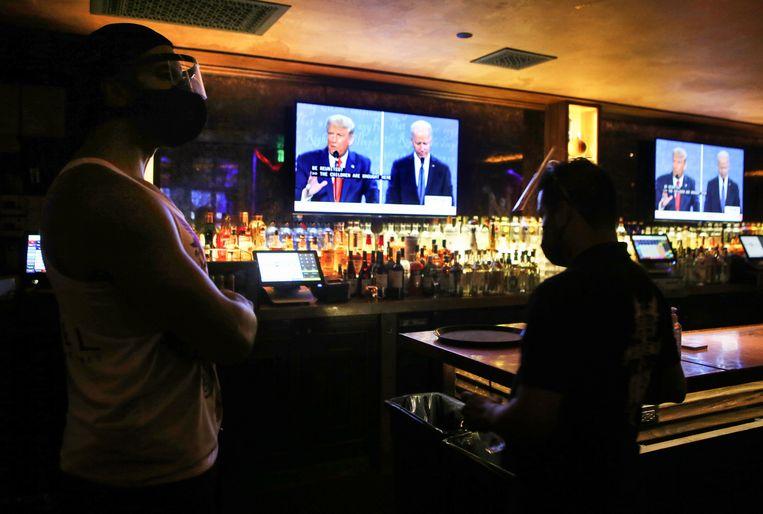 Werknemers in een bar in Hollywood in Los Angeles kijken haar het debat. Beeld Getty Images