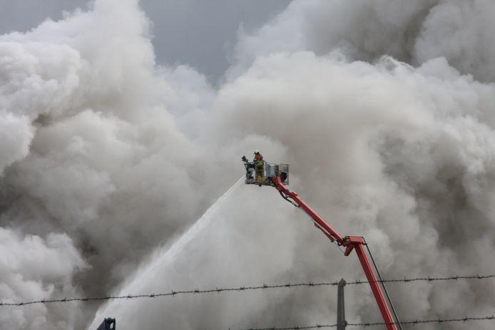 Brandweer zet hoogwerkers in om brand bij A.V.I onder controle te krijgen.
