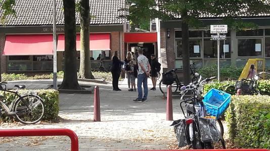 Ouders en kinderen komen basisschool de Korenaer uit, nadat ze zijn bijgepraat in de aula.