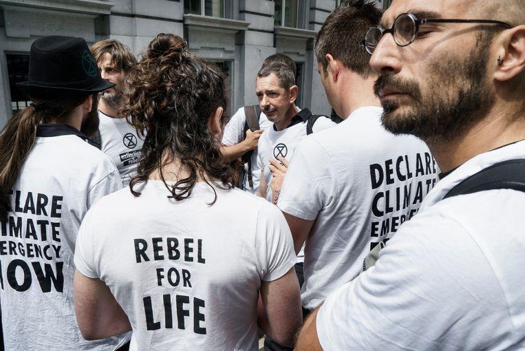 Activisten overleggen: naar huis gaan of blijven protesteren en een aanhouding riskeren. Beeld Eric de Mildt