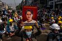 Een demonstrant in Yangon houdt een beeltenis van de opgepakte regeringsleider Aung San Suu Kyi in de lucht.