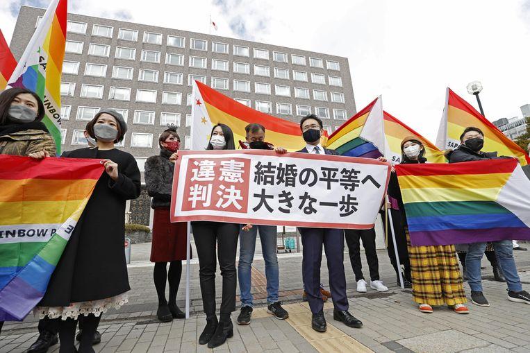 Mensen demonstreren buiten de rechtbank van Sapporo met spandoeken waarop staat dat het ongrondwettelijk is dat Japanse koppels van hetzelfde geslacht niet kunnen trouwen. Beeld REUTERS