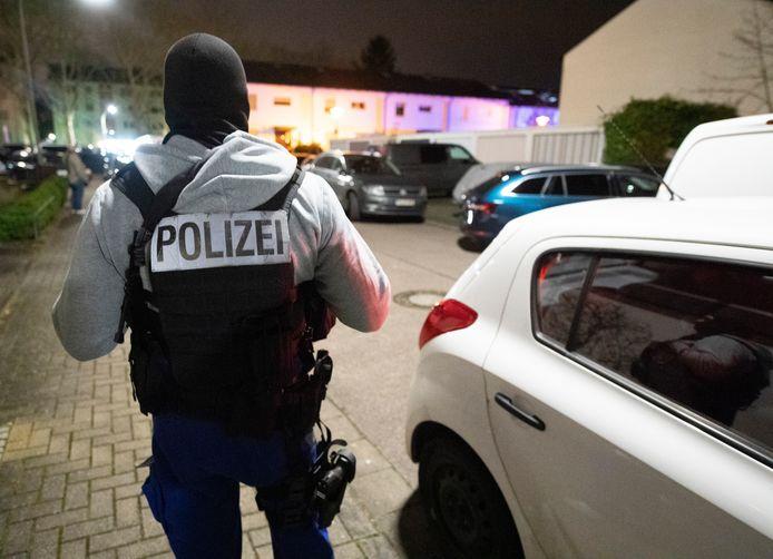 Een Duitse politieman staat op wacht bij de de bar waar verschillende mensen werden doodgeschoten.