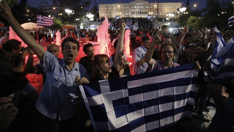 Aanhangers van het 'nee' kamp vieren feest in Athene, nadat de eerste uitslagen over het referendum bekend zijn geworden. Beeld epa