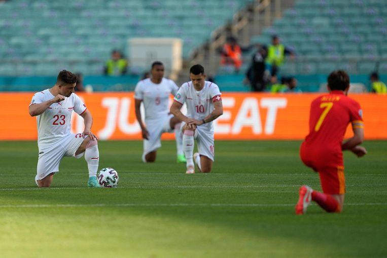 Zowel de spelers van Zwitserland (wit) als die van Wales (rood) knielden voor hun eerste wedstrijd. Beeld AFP