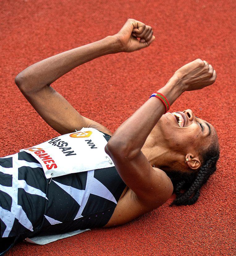 Sifan Hassan heeft een nieuw wereldrecord gelopen en ligt uitgeput op de grond. Beeld Klaas Jan van der Weij / de Volkskrant
