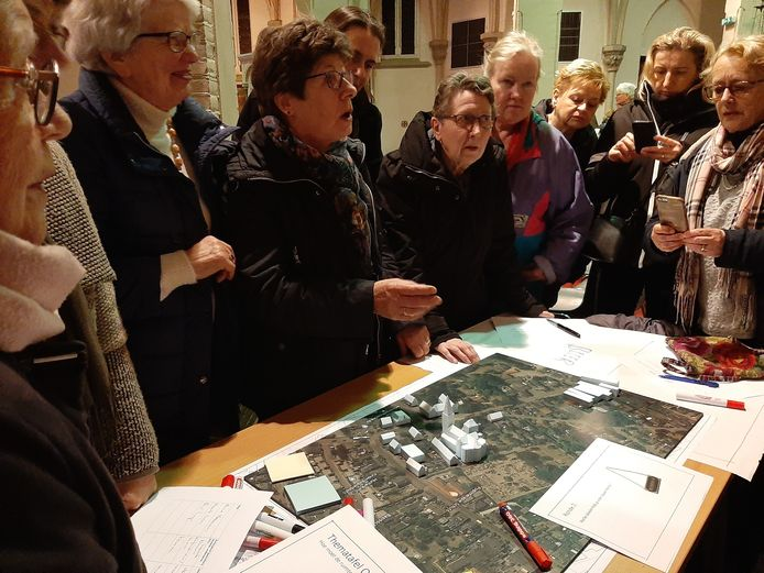 Bewoners bespreken bij een maquette waar er op het terrein van de kerk gebouwd zou kunnen worden.