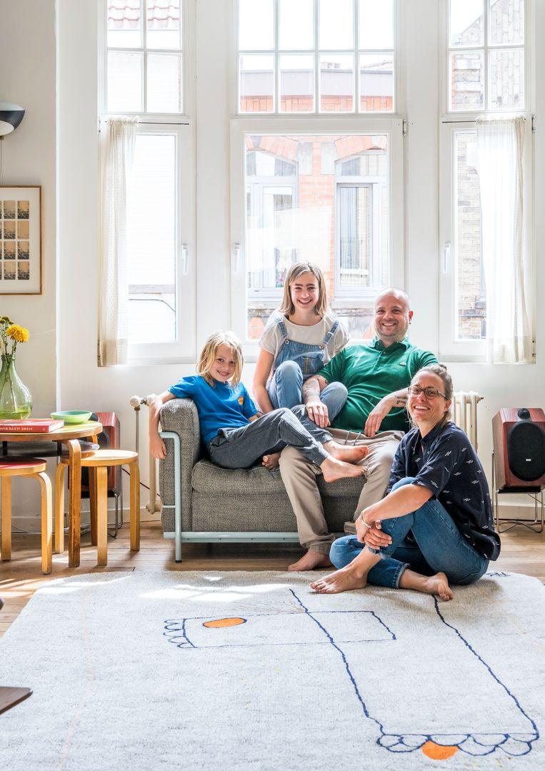Rufus, Charlie, Pieter en Sara in hun living op de eerste verdieping. Het tapijt is een ontwerp van Pieter. De zetel is een Cassina-reëditie van Le Corbusier. Beeld Luc Roymans
