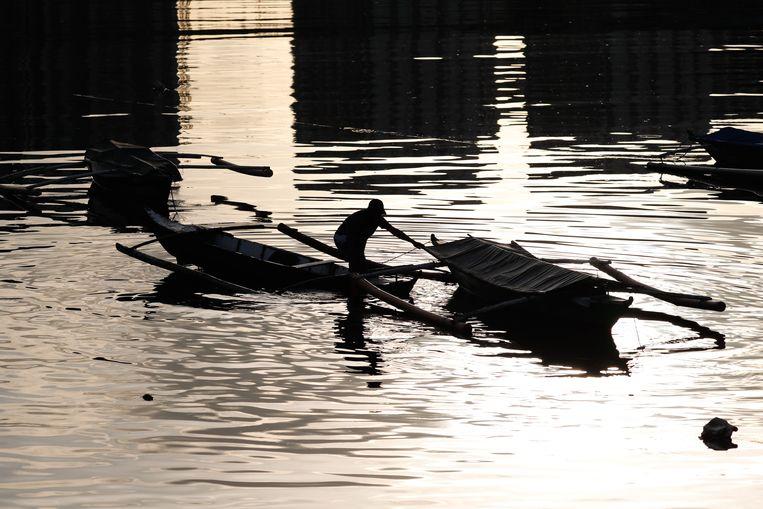 Een visser brengt zijn bootjes in veiligheid voor de naderende storm. Beeld EPA