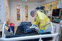 Verpleegkundige Nicole (22) maakt een bed schoon.