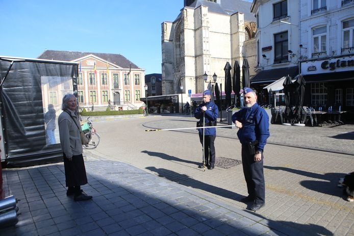 De politie toont de voorbijgangers op de Markt met middel van een stok wat de minimumafstand is.