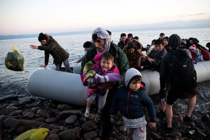 Afghanen en hun kinderen meren met hun hebben en houden aan op een strand in Lesbos nadat ze met een rubberbootje de Egeïsche Zee overstaken.