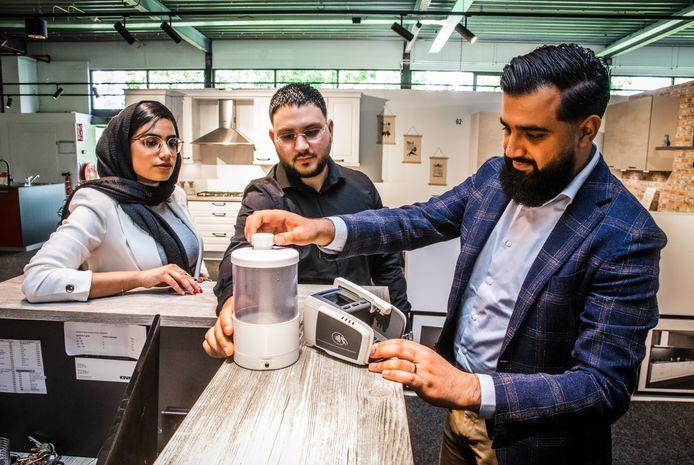 Ahmad Mohemmed (rechts) demonstreert met vriend Levon en zus Sukena hun uitvinding Pinbeurt.