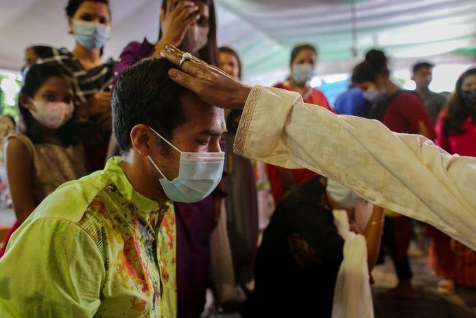 Люди надевают маски во время посещения храма в Дакке, Бангладеш.