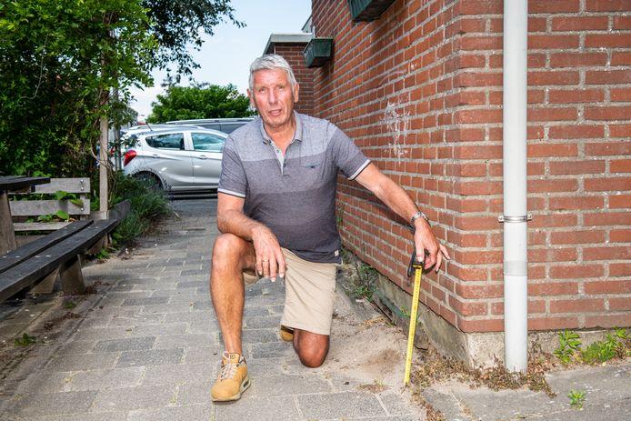 Erik Kerkman laat zien hoe ernstig de verzakking is bij de huizen en schuurtjes aan de Boterbloemweg in Alphen aan den Rijn