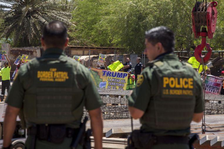 Amerikaanse grensagenten kijken naar een demonstratie tegen Trumps asielbeleid aan de Mexicaanse kant van de grens. Archiefbeeld. Beeld AFP