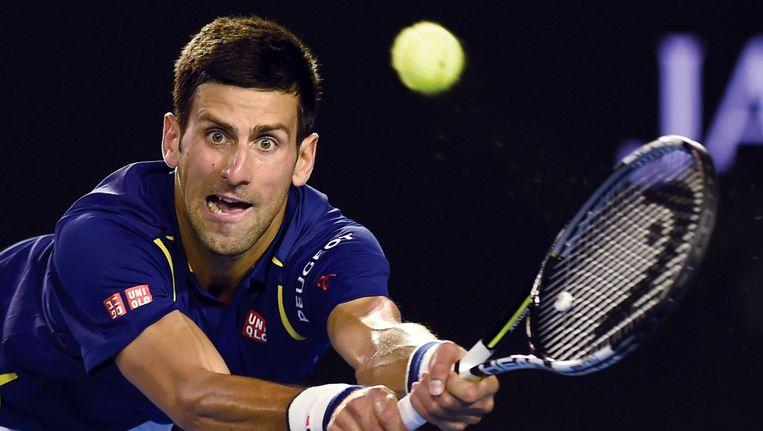 Novak Djokovic retourneert de bal tijdens zijn partij tegen Roger Federer in Australië. Federer heeft het moeilijk, hij verloor de eerste twee sets. Beeld ap