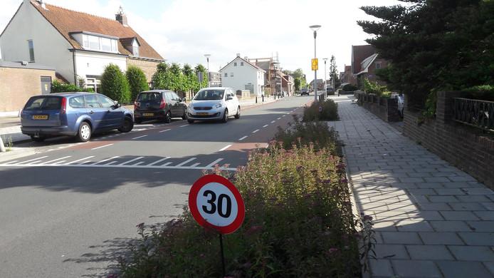 Bewoners hebben bordjes opgehangen in de Burgemeester van Loonstraat om het verkeer langzamer te laten rijden.