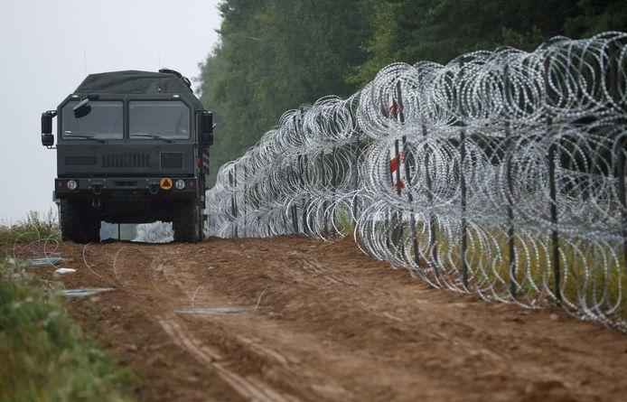 Un véhicule à côté d'une clôture construite par des soldats polonais à la frontière entre la Pologne et le Bélarus