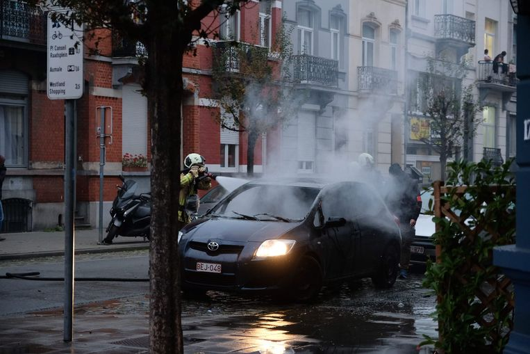 Actie voor Adil ontaardt: brandweerdiensten blussen een brandende wagen. Beeld Marc Baert