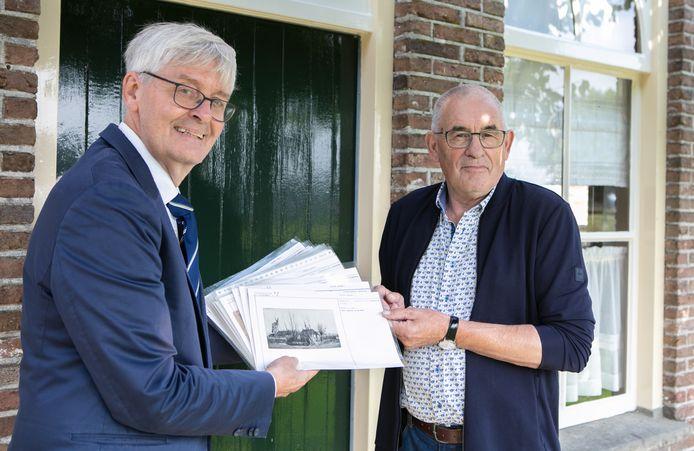 Wethouder Ko Scheele overhandigt een aantal oude foto's aan Berend Jan Warmelink. In totaal zijn het er 14.000.