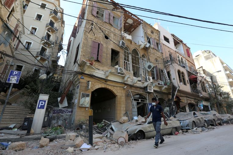 Een inwoner loopt in een getroffen straat in Beiroet. Beeld REUTERS