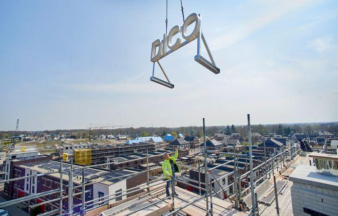 Met een speciale kraan worden de letters DICO neergezet op het appartementengebouw in het Land van Dico, het hoogste punt van de nieuwbouwwijk. Uitvoerder Hans Verbruggen geeft aanwijzigen.