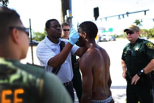 Een ambulance-medewerker controleert een man die mogelijk flakka heeft gebruikt op het strand van Pompano, Florida.