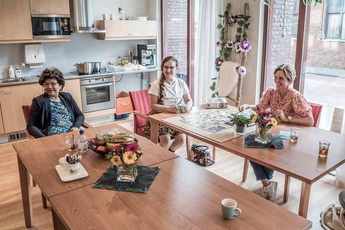 Ria (70) en Wilma (63) nemen samen met Wendy Jansen, de groepsbegeleider, het nieuws van de dag door.