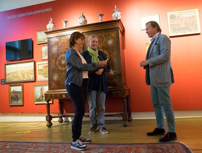 Cindy Brouwer en Veronica Frenks (vlnr)  van het Veers Museum bekijken het doosje nadat ze het kregen van Tjep van Voorst Vader.