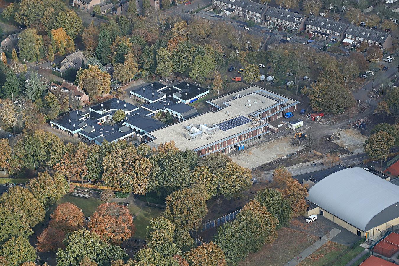 De plek waar het nieuwe gezondheidscentrum in Waalre-dorp eind 2020 moet verrijzen: binnen de driehoek van bomen in het midden onderaan op de foto.