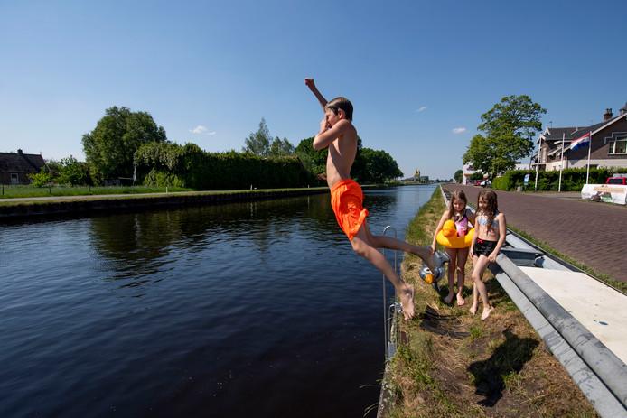 Nathanya Bom, 9 jaar (met pinguïn zwembandje) en haar 12-jarige broer Nathaniël uit Vriezenveen nemen samen met hun nichtje Chanel een verfrissende duik in het kanaal bij Vriezenveen.