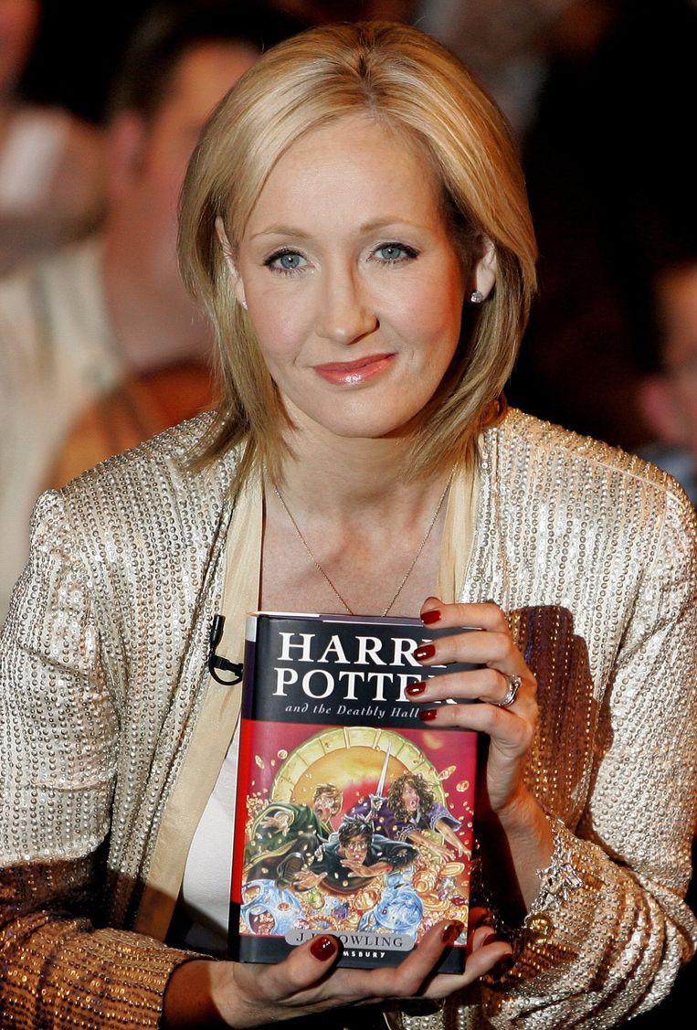 De Britse schrijfster J. K. Rowling met een van de boeken uit de reeks. Beeld AP