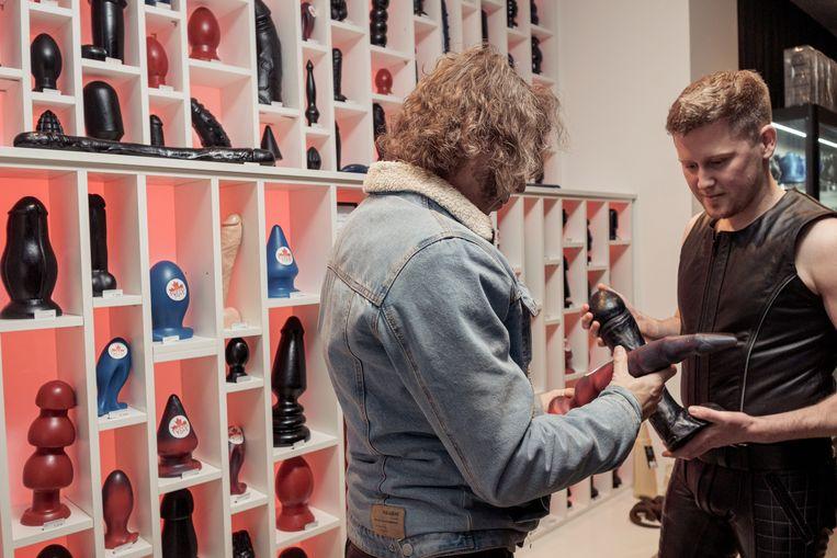 De wand met vanachter verlichte dildo's zou niet misstaan in het Stedelijk Museum. Beeld Jakob Van Vliet