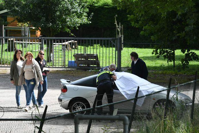 De politie heeft de voorruit van de auto afgedekt met een wit doek.