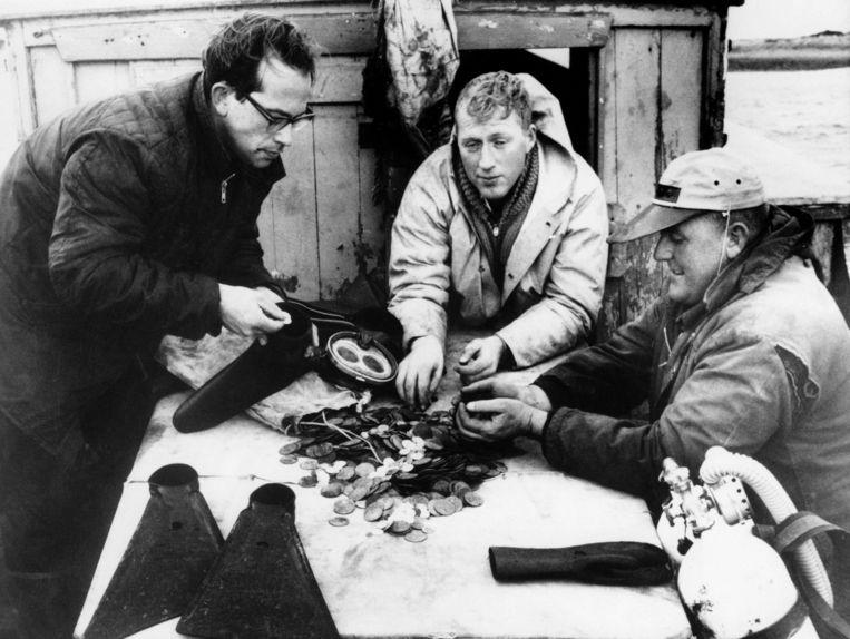 Alex Storm (l.) en zijn collega-schattenzoekers monsteren een lading munten uit het wrak van de 18de-eeuwse driemaster Chameau. Beeld Argosy Photo, via United Press International