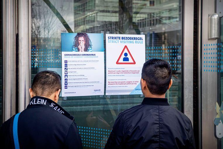 Bezoekers van het ErasmusMC in Rotterdam lezen de bezoeks- en gedragsregels. Beeld BSR Agency