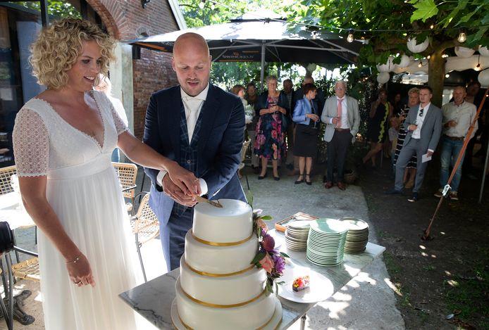 Kitty Buil en Daan Koenders snijden de trouwtaart aan na de huwelijksceremonie.