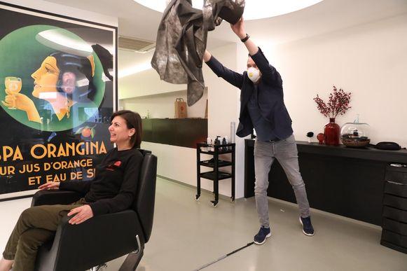 Kapper Yvan probeert de kappersschort vanop anderhalve meter afstand over zijn klant te gooien