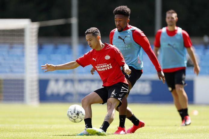 Chris Gloster en Mauro Júnior in gevecht om de bal bij PSV.